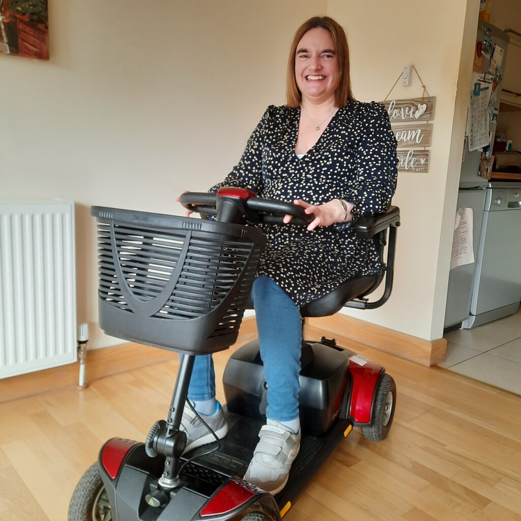 A woman sits on a red mobility scooter with a basket on the front. She is inside a house or apartment and smiling at the camera.